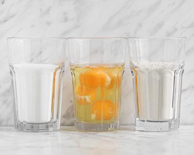 Tre glas, ett med ägg, ett med vetemjöl och ett med socker.