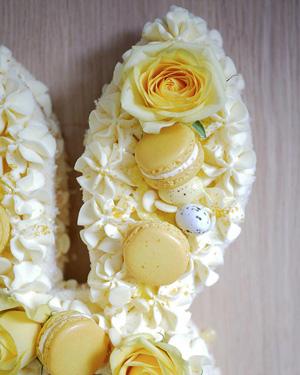 Detaljer på gul påsktårta, macarones och rosor.