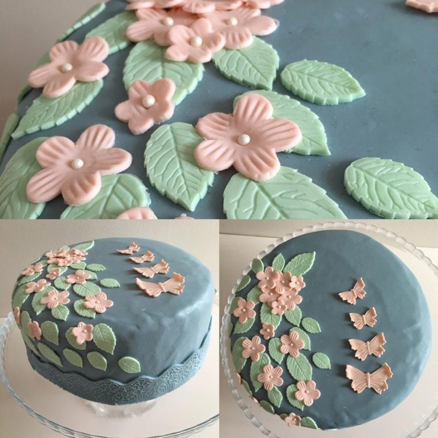 Blå marsipantårta dekorerad med blommor och fjärilar i sockerpasta.