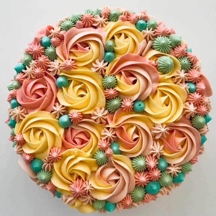 Färgglad påsktårta spritsat i rosa, grönt och gult