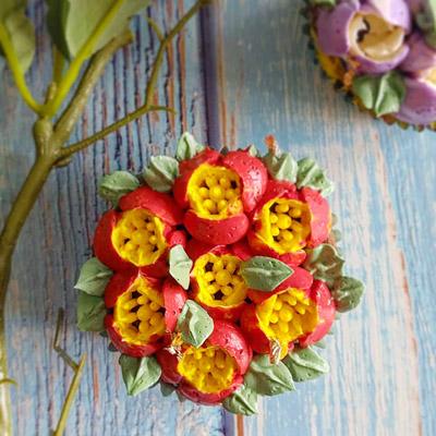 Röda och gula blommor spritsade på cupcakes.