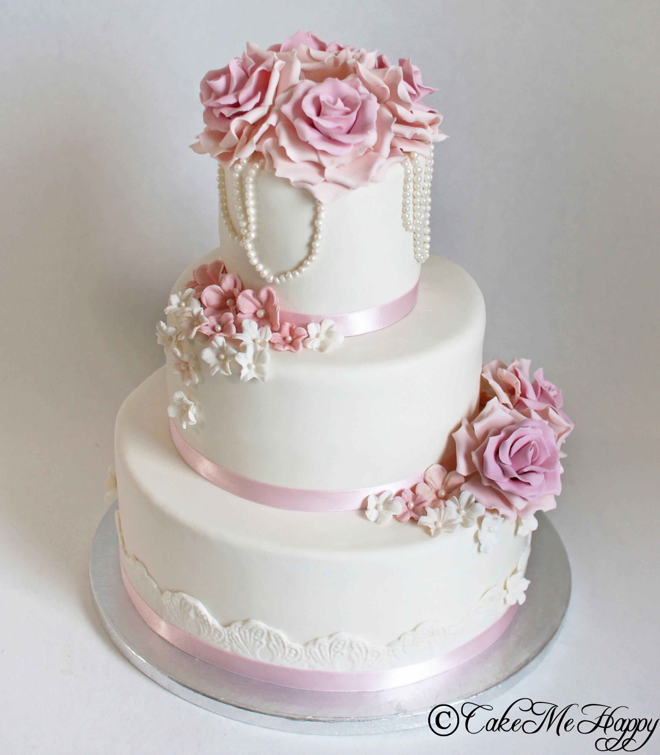 Vit bröllopstårta med rosa detaljer