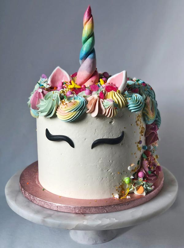 Unicorn tårta med horn i flera färger.